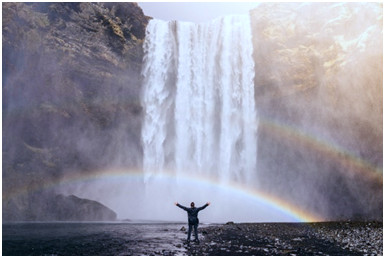 enjoying life outside your business: Man celebrating success under a waterfall with a double rainbow